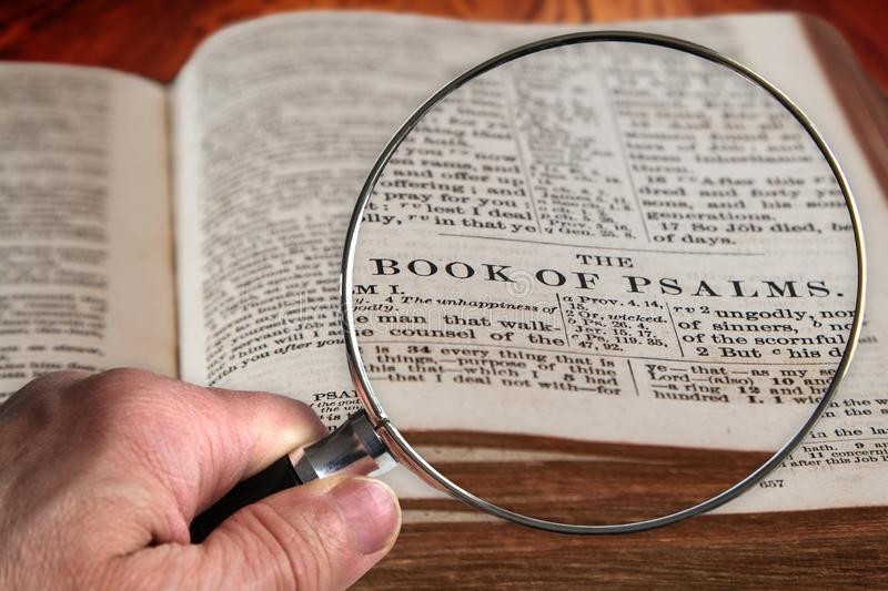 Magnifying Glass on Famous Bible Chapter of Psalms. Hand holding magnifying glass over an old Bible opened to the famous book of Psalms. This translation is King royalty free stock image