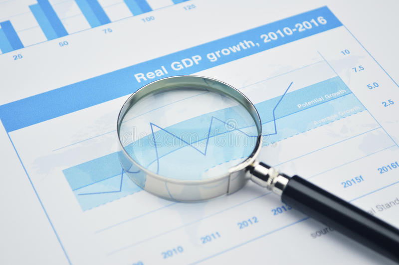 Magnifying glass on financial graph, accounting background stock images