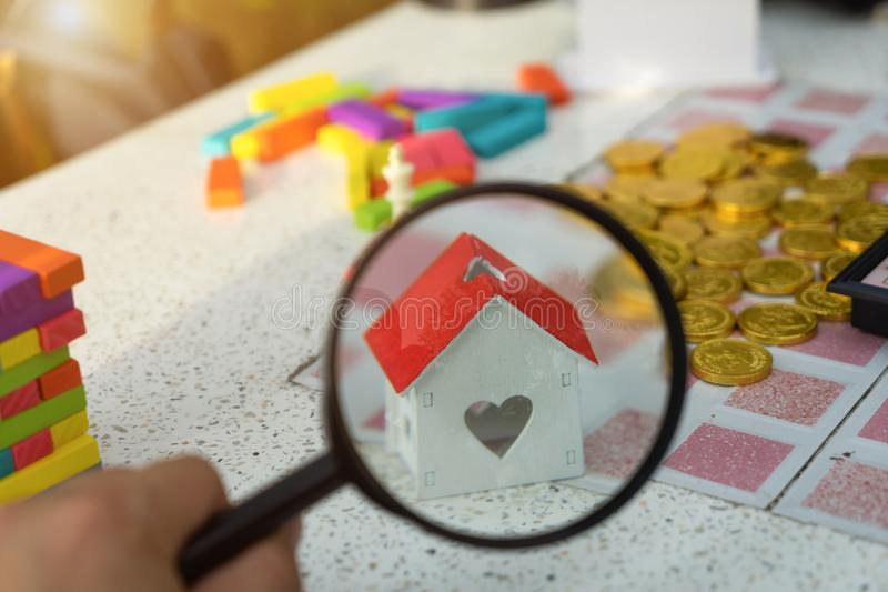 Magnifying glass focus on house model on golden coins money, rea royalty free stock photography