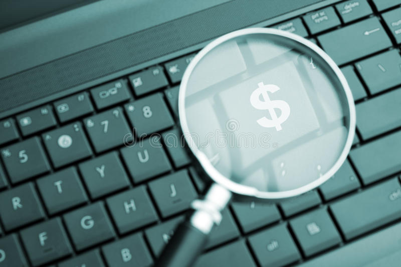 Magnifying glass focused on the $ button. Toned in blue stock images