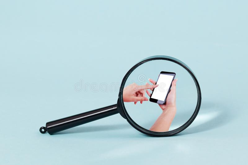 Magnifying glass over person using smartphone. A magnifying glass focusing over the hands of a person using a smartphone royalty free stock images