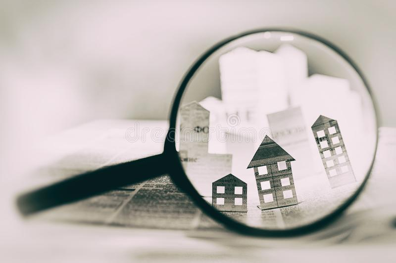 Magnifying glass in front of an open newspaper with paper houses. royalty free stock image