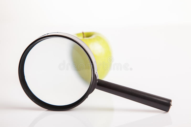 Magnifying glass with green apple stock photography