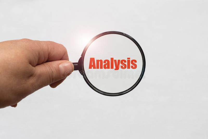 Magnifying glass in hand and a Analysis word on the white background stock photo