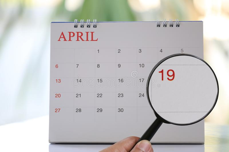Magnifying glass in hand on calendar you can look Nineteenth day. Of month,Focus number nineteen in April,Concept in business and meetings stock image