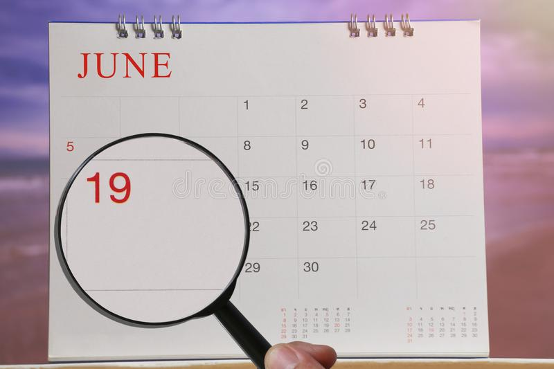 Magnifying glass in hand on calendar you can look Nineteenth day. Of month,Focus number nineteen in June,Concept in business and meetings stock photo
