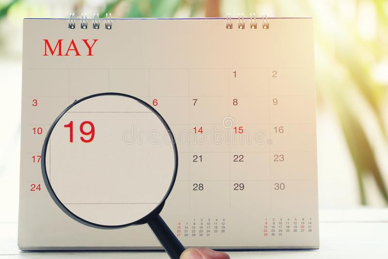 Magnifying glass in hand on calendar you can look Nineteenth day. Of month,Focus number nineteen in May,Concept in business and meetings royalty free stock photography