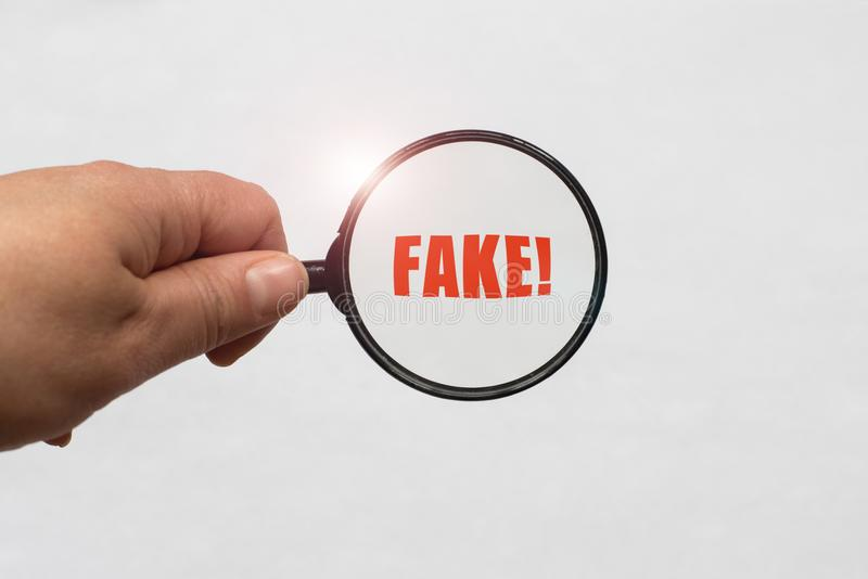 Magnifying glass in hand and a Fake word on the white background stock images
