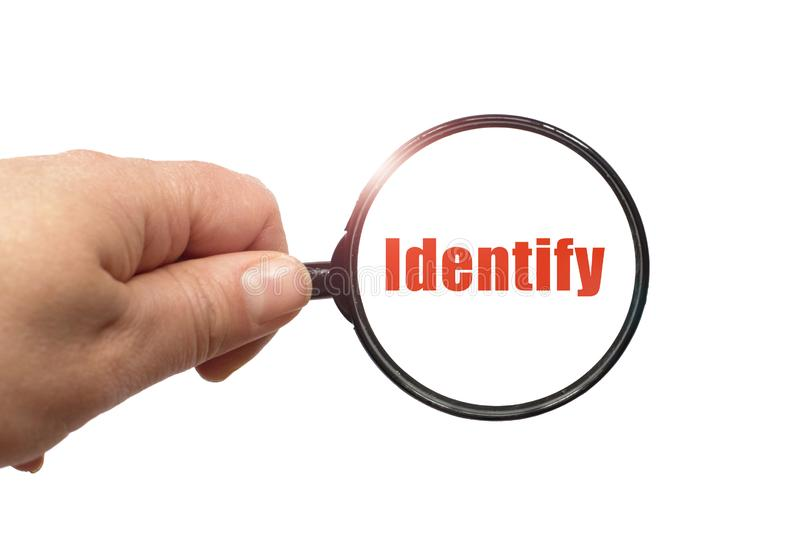 Magnifying glass in hand and a identify word on the white background royalty free stock images