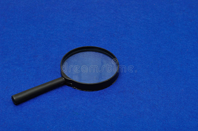 Magnifying glass. Isolated on a blue background stock photos