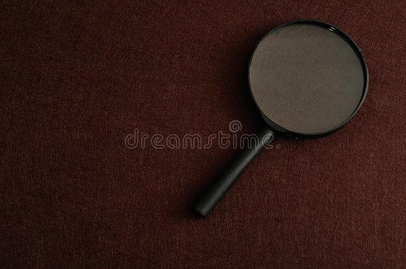 Magnifying glass. Isolated on a brown background stock photo