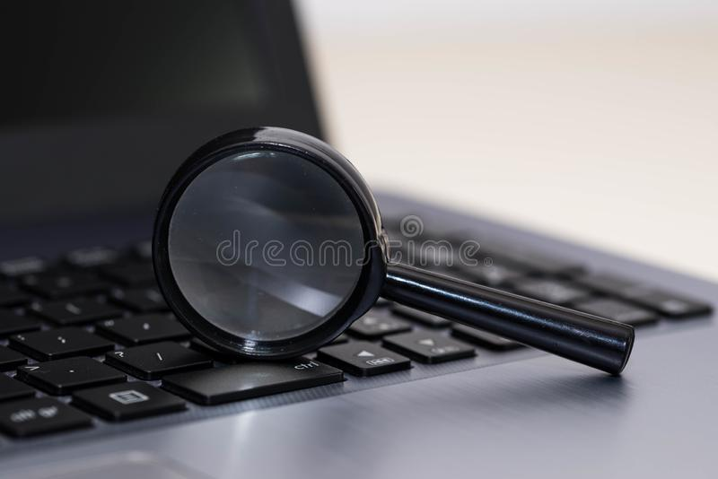 Magnifying glass on laptop computer keyboard stock image