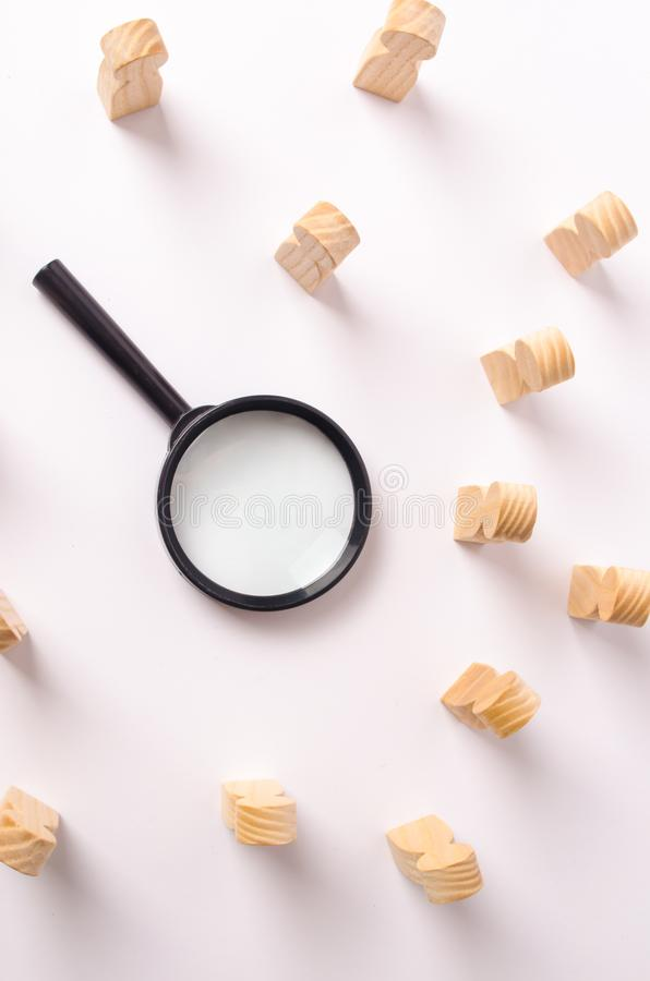 A magnifying glass lies in the center of the wooden figures of people who look at it. The concept of the search for workers stock photography