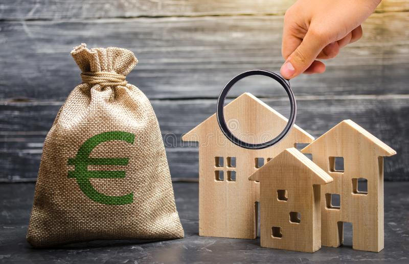 Magnifying glass is looking at a bag with euro money and three houses. Affordable cheap loan, mortgage. Taxes, rental income. royalty free stock image