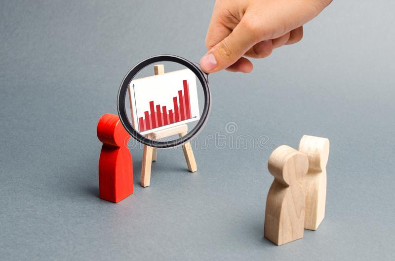 Magnifying glass is looking at the businessman reports to his staff at a briefing, a discussion of the business strategy stock images