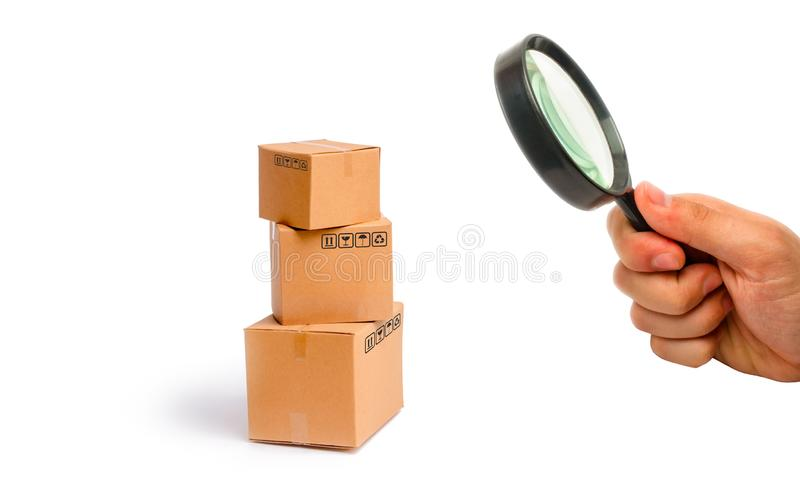 Magnifying glass is looking at the Cardboard boxes on a white background. The concept of packing goods, sending orders. To customers. Warehouse of finished royalty free stock photos