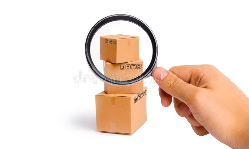 Magnifying glass is looking at the Cardboard boxes on a white background. sending orders to customers. Warehouse of finished. Products and equipment. Moving to stock photo