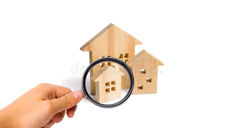 Magnifying glass is looking at the City of wooden houses on a white background. The concept of urban planning, infrastructure proj. Ects. Buying and selling real royalty free stock photography