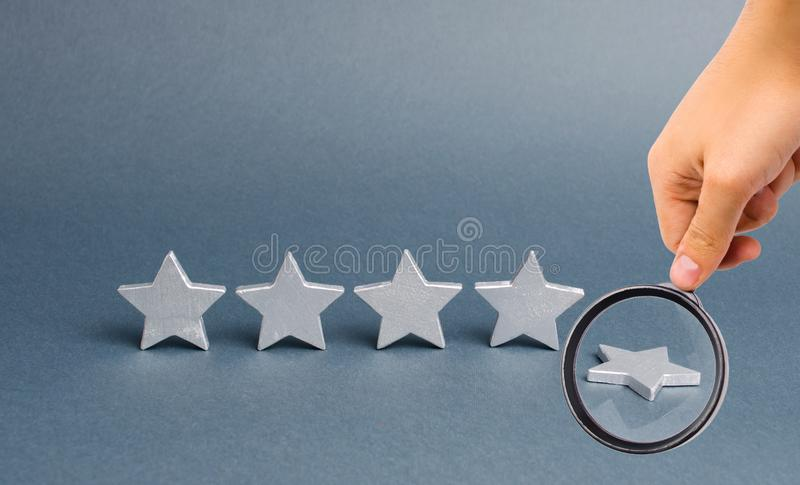 Magnifying glass is looking at five silver stars, one star fell. Loss of rating and level, reducing prestige and reputation royalty free stock images