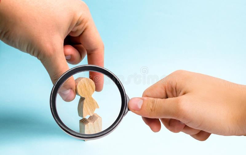 Magnifying glass is looking at the hand of the person collects a figure of the person together. Psychological assistance. And support. Treatment of stock photo