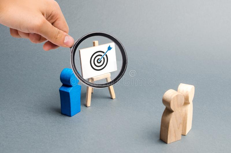 Magnifying glass is looking at leader explains employee tactics of advertising targeting. Training, briefing. Search strategies. For effective advertising royalty free stock image