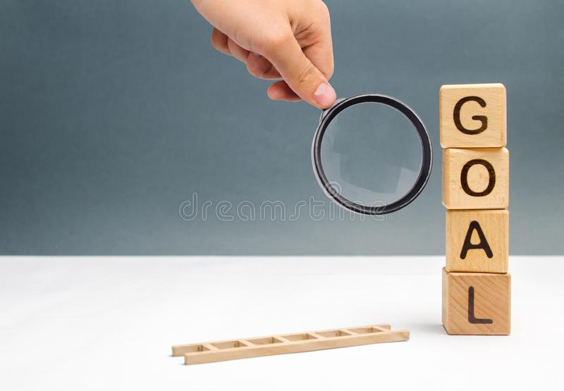 Magnifying glass is looking at the missing ladder near tower of cubes with an inscription goal and a fallen ladder. achieving. The goal, subject to the royalty free stock photo