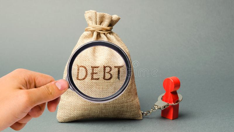 A magnifying glass is looking at a money bag with the word Debt and a borrower is bound by handcuffs. Mandatory payment of debt. Alimony payment. Pay of a royalty free stock photo