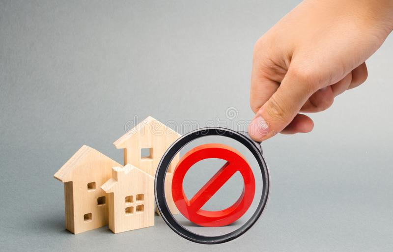 Magnifying glass is looking at the No Sign and the wooden house. Unavailability of housing, busy or low supply. Inaccessible. And expensive housing. Seizure and royalty free stock photo