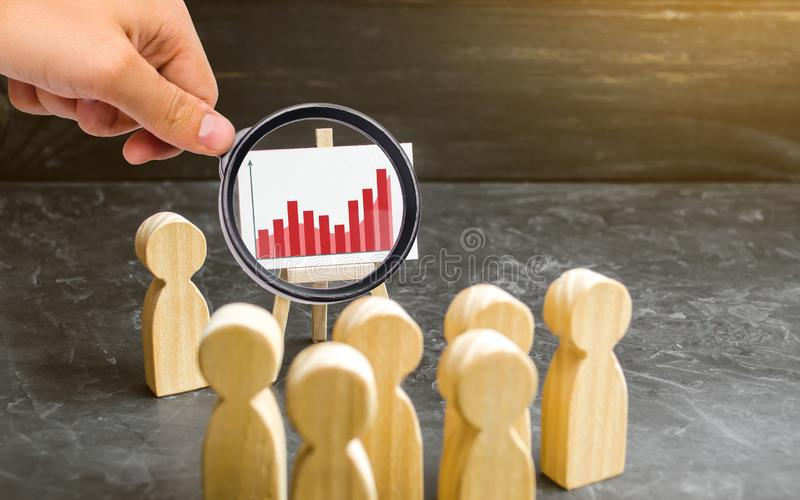 Magnifying glass is looking at the people gathered for a meeting or speech of the leader. Profit and income analysis, briefing. royalty free stock photos