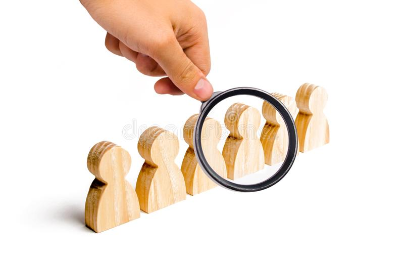 Magnifying glass is looking at the People stand in a formation on a white background. Discipline and order, submission. In anticipation of an order. The stock photo
