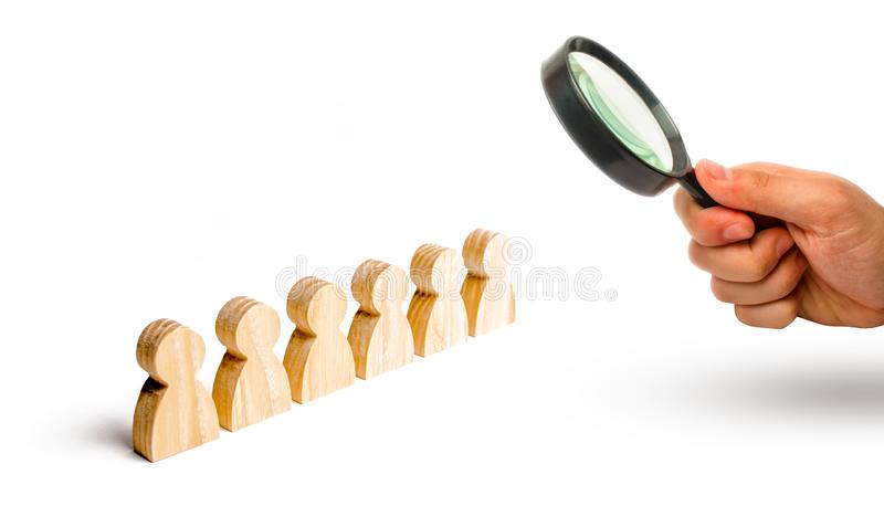Magnifying glass is looking at the People stand in a formation on a white background. Discipline and order, submission. In anticipation of an order. The royalty free stock image