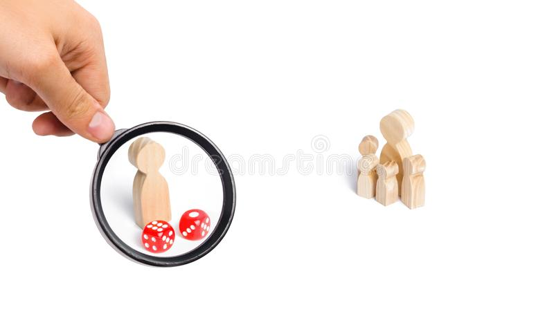 Magnifying glass is looking at the People are standing near dice. The family stands near the dice cubes. The concept of gambling. The dependence on gambling stock photo