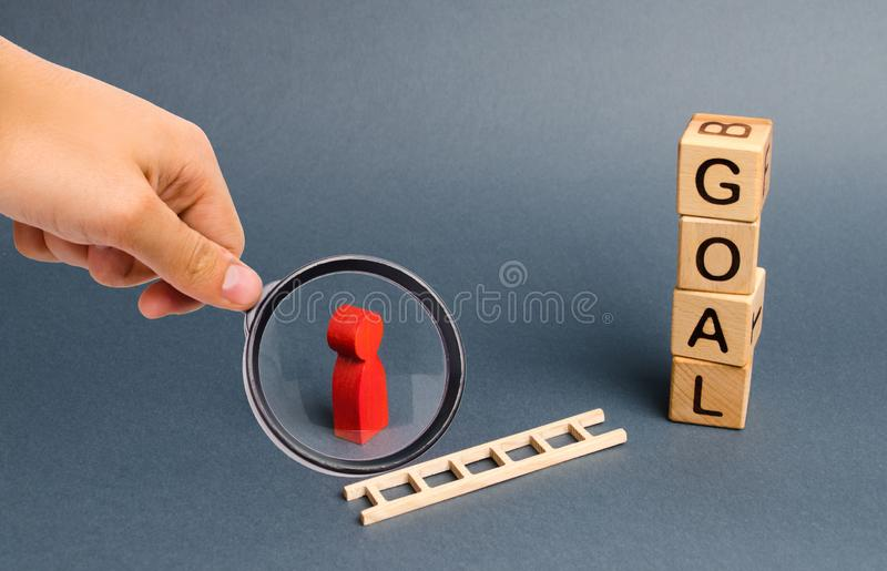 Magnifying glass is looking at a red figure of a man stands near fallen ladder and a tower of cubes with an inscription goal. Achieving the goal, subject to royalty free stock image