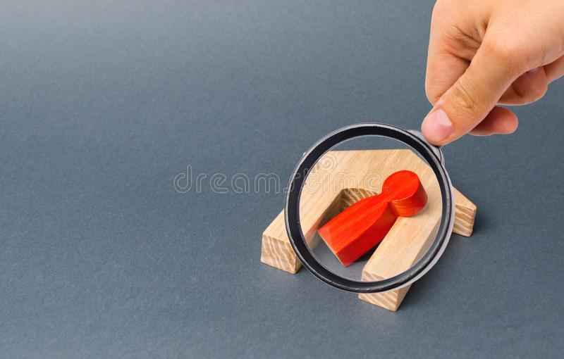 Magnifying glass is looking at a red figurine of a man and a fallen house on a gray background. accident or disaster. stock photo