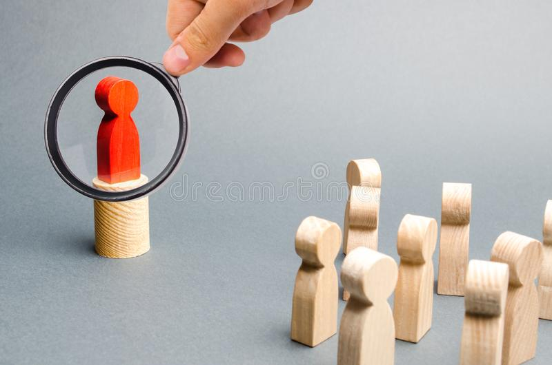 Magnifying glass is looking at the red man stands on the podium and appeals to the crowd of people. Agitation, appeal and appeal. To the crowd. Leader and stock photos