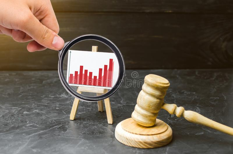 Magnifying glass is looking at the stand information graphics and a wooden hammer of a judge. Rising crime. Improving efficiency. Of the judicial system stock image