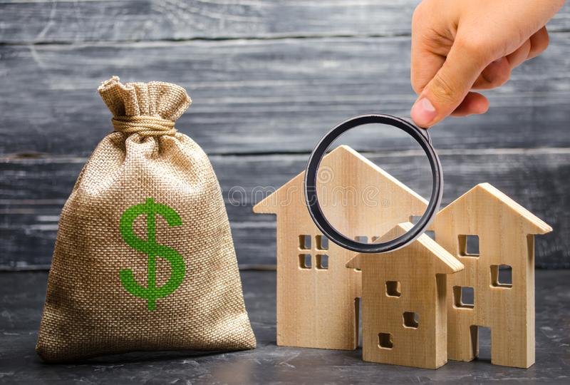 Magnifying glass is looking at the three houses near a bag with money. real estate acquisition and investment. Affordable cheap loan, mortgage. Taxes, rental royalty free stock image