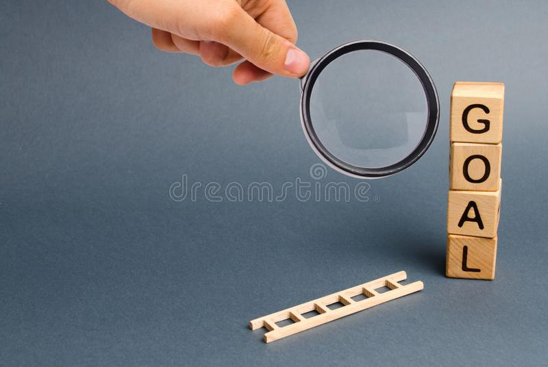 Magnifying glass is looking at a tower of cubes with an inscription goal and a fallen ladder. Tool for success. Don`t give up. Half way. achieving the goal royalty free stock images