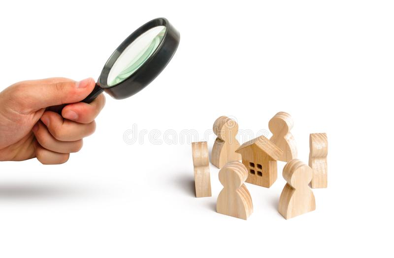 Magnifying glass is looking at the Wooden figurines of people stand around the house. Search for a new home and real estate. Buying or selling a home. Moving royalty free stock image