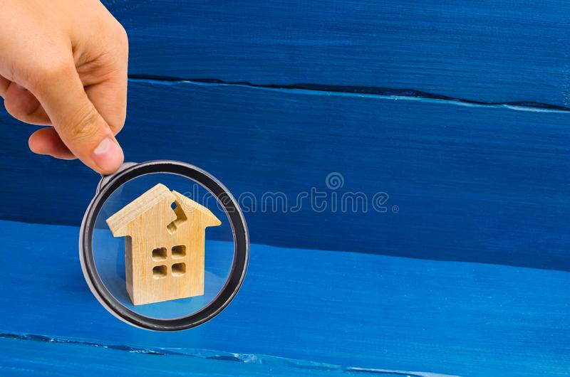 Magnifying glass is looking at the wooden house with a crack. The concept of a damaged house, dilapidated housing. Renovation. Repair and restoration of the stock image