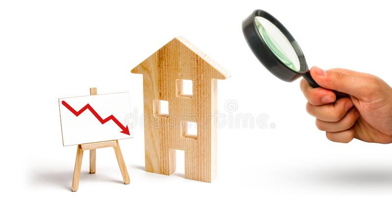 Magnifying glass is looking at the wooden house and red arrow down. concept of falling prices and demand for real estate, the fall royalty free stock photography