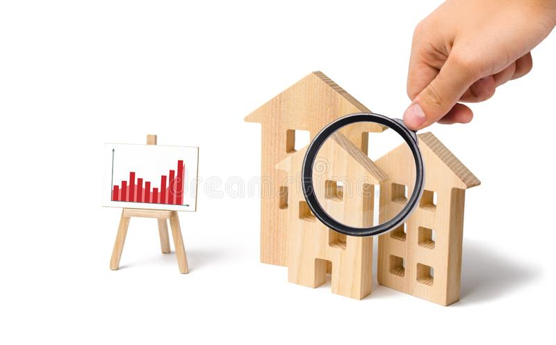 Magnifying glass is looking at the wooden houses with a stand of graphics and information. Growing demand for housing. And real estate. Statistics on the state royalty free stock photos