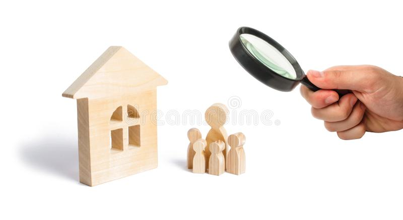 Magnifying glass is looking at the young family with children is standing near a wooden house. concept of a strong family, royalty free stock image