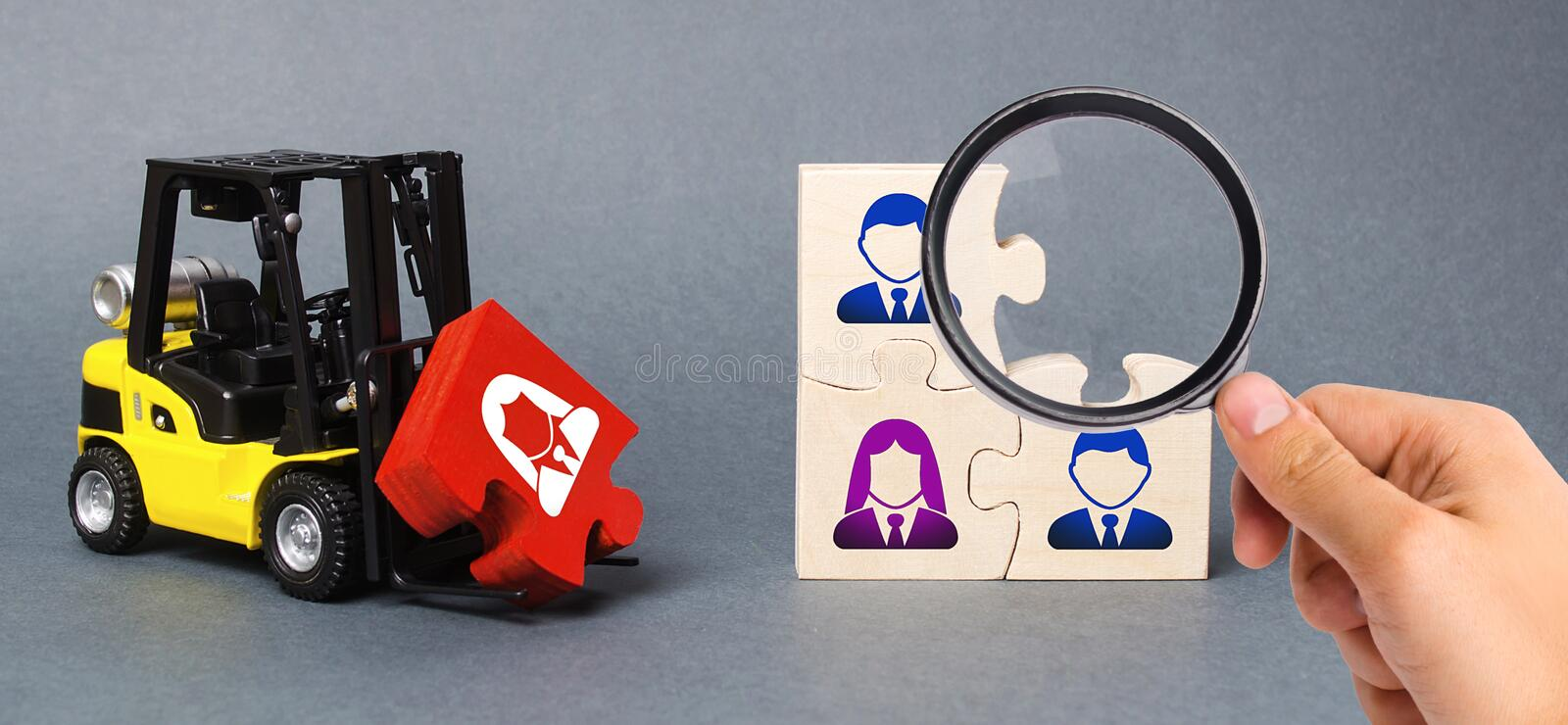 A magnifying glass looks at a red puzzle to the unfinished assembly of business team. Search, recruitment staff, hiring leader. Creating an efficient and royalty free stock photos