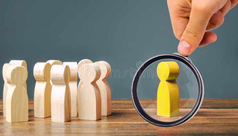 A magnifying glass looks at a yellow figurine of a man stands aside from the crowd of people. Asociality, sociopathy. Rejected. From society, lonely stock photos