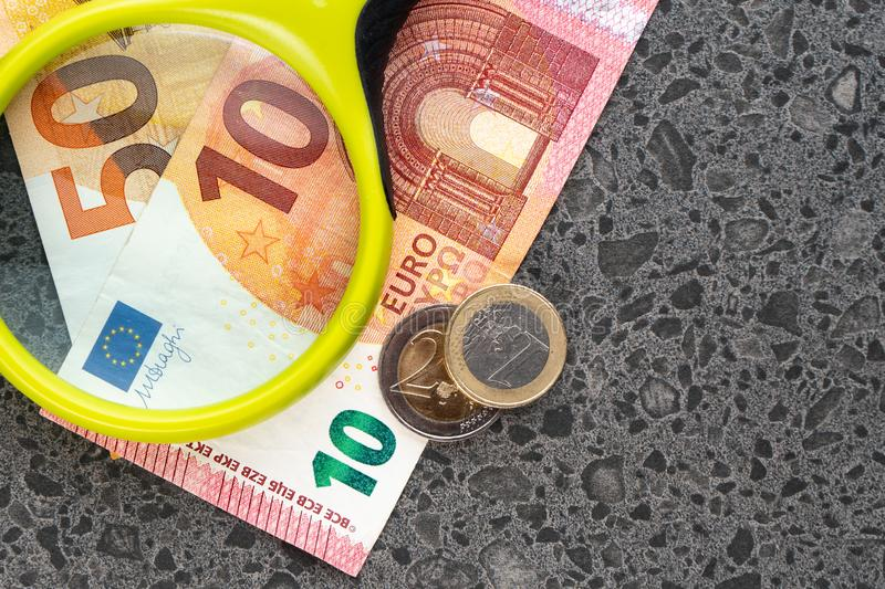 Magnifying glass and money euro isolated on stone background. Bancnots stock images