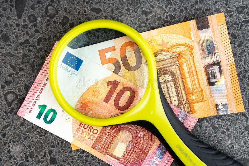 Magnifying glass and money euro isolated on stone background. Bancnots royalty free stock photo