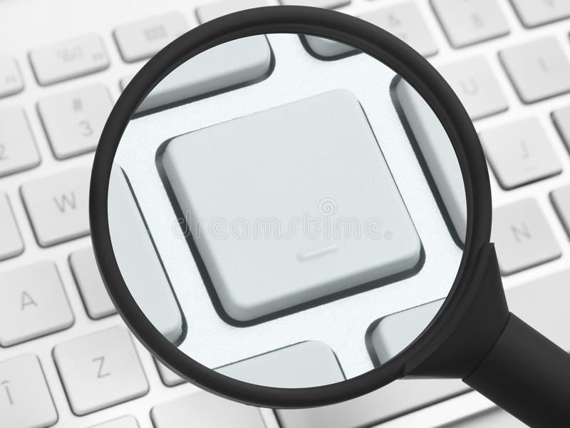 Magnifying glass over a computer keyboard royalty free stock photography