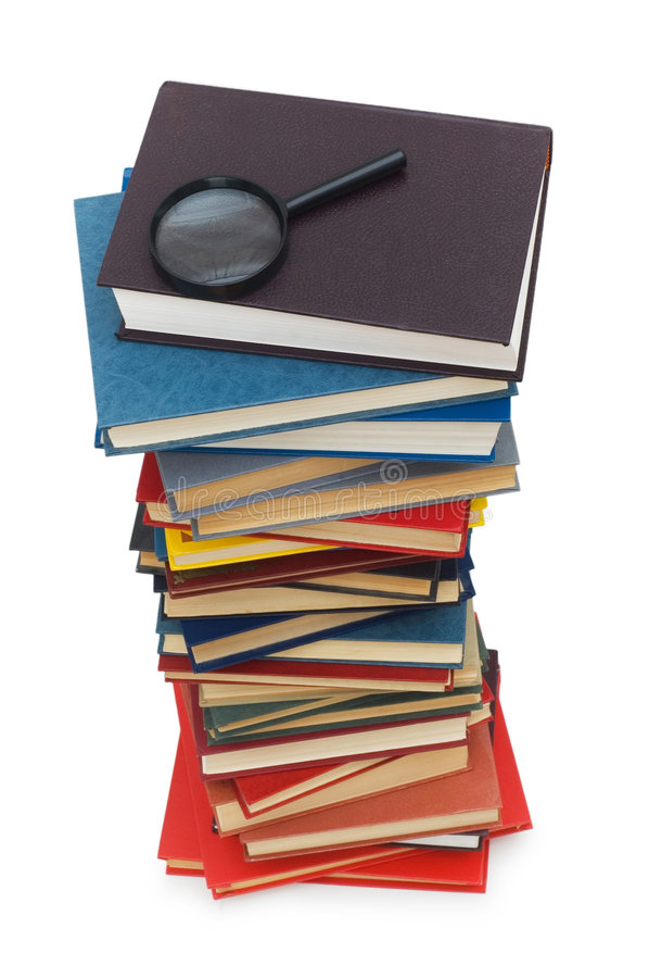 Magnifying glass over the stack of books royalty free stock photo