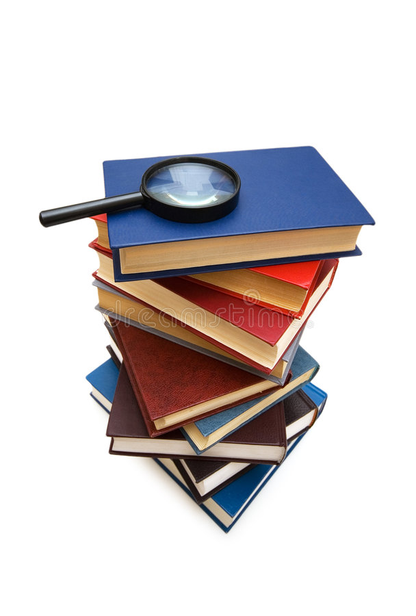 Magnifying glass over the stack of books royalty free stock photography